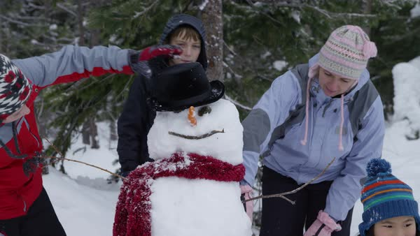 Mother and kids working on snowman together Royalty-free stock video