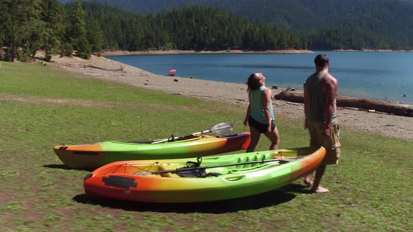 Couple carry kayaks to lake Royalty-free stock video