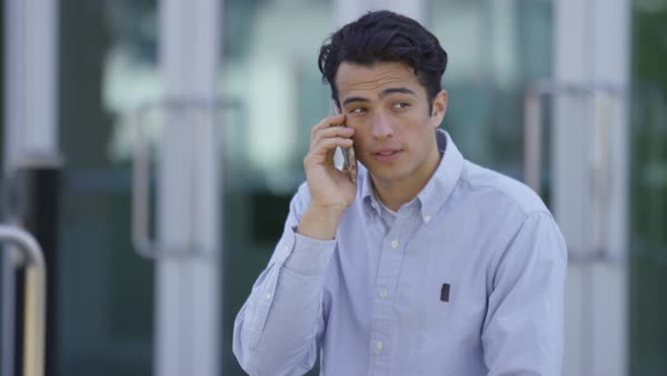 Young businessman talking on cell phone outdoors Royalty-free stock video