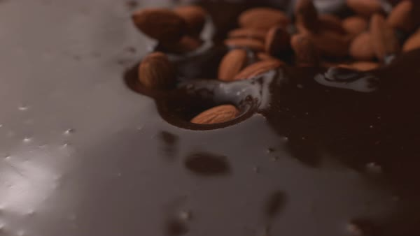 Almonds falling into chocolate in super slow motion Royalty-free stock video