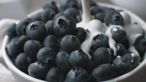 Pouring cream onto blueberries in super slow motion Royalty-free stock video