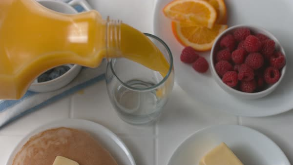 Pouring glass of orange juice at breakfast in super slow motion Royalty-free stock video