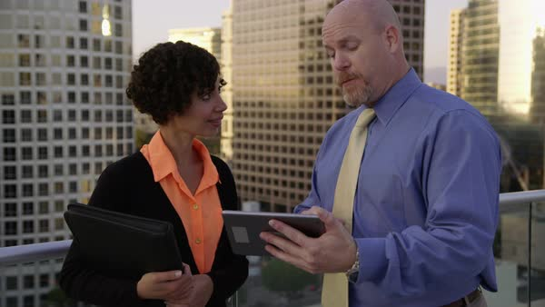 Businesspeople outdoors on rooftop look at digital tablet together Royalty-free stock video