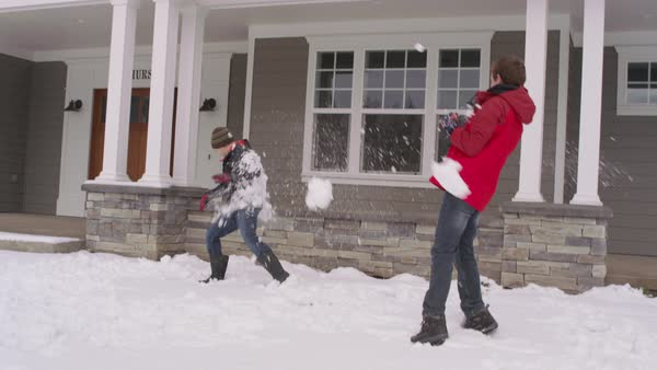 Boys having snow ball fight by home in winter Royalty-free stock video