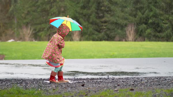 Young girl with umbrella playing in rain Royalty-free stock video
