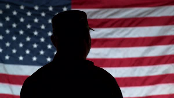 Silhouette of soldier saluting with American flag in background Royalty-free stock video