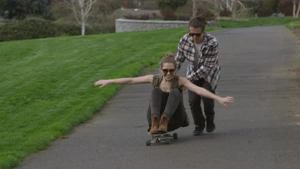 Teen pushing girl on skateboard at park Royalty-free stock video