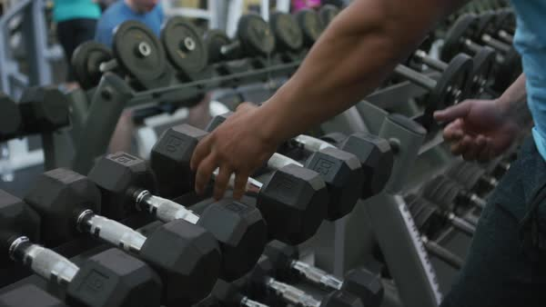Muscular man picks up weights at gym Royalty-free stock video