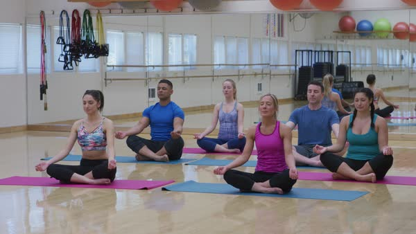 Group of men and women sitting on floor doing yoga at studio Royalty-free stock video