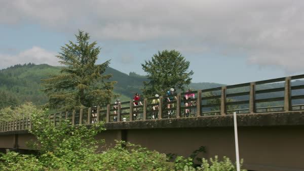 Group of cyclists on road ride over bridge Royalty-free stock video