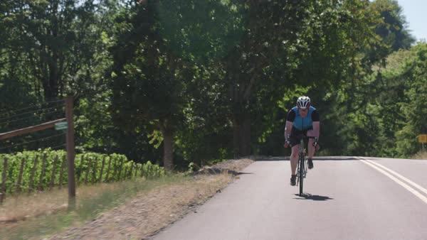 Tracking shot of a male cyclist on country road Royalty-free stock video