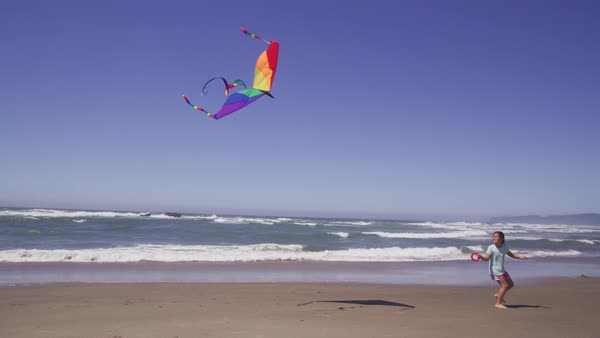 Young girl flying kite at beach Royalty-free stock video