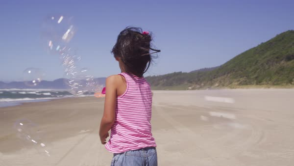 Young girl playing with bubbles at beach Royalty-free stock video