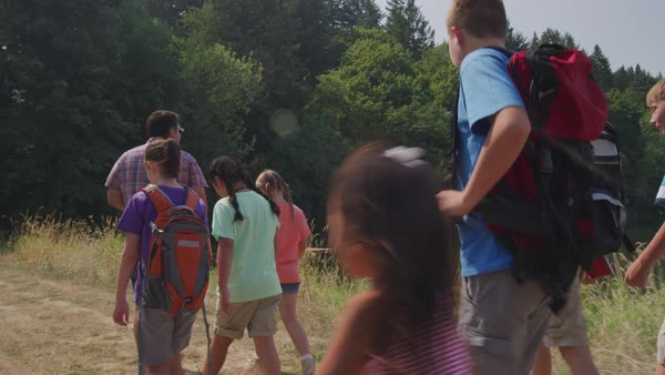 Kids at summer camp hiking by pond with leader Royalty-free stock video