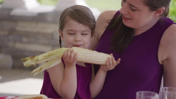 Young girl eating corn at backyard barbeque Royalty-free stock video