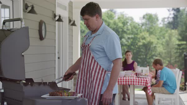 Man cooking with grill at backyard barbeque Royalty-free stock video