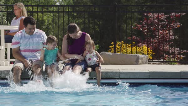 Family splashing feet in backyard pool Royalty-free stock video