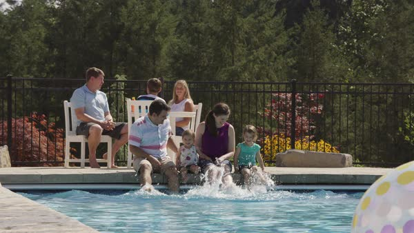 Family splashing feet in backyard pool, slow motion Royalty-free stock video