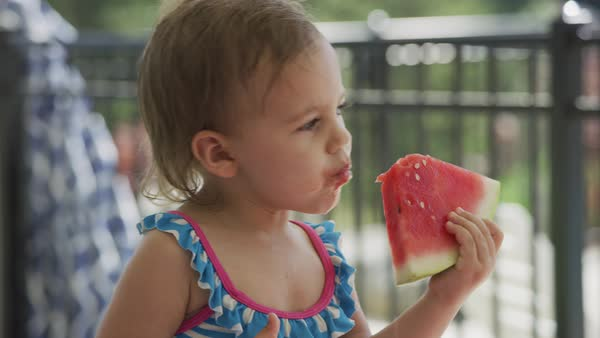 Young girl eating watermelon at backyard barbeque Royalty-free stock video