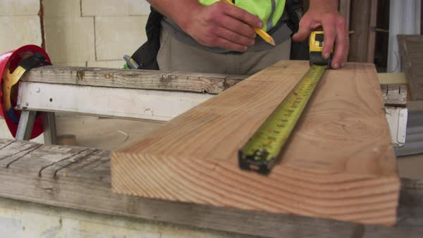 Construction worker measuring and marking lumber Royalty-free stock video