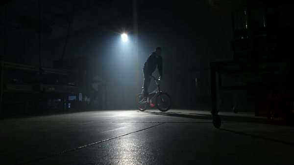 BMX rider doing tricks in dark warehouse. Royalty-free stock video