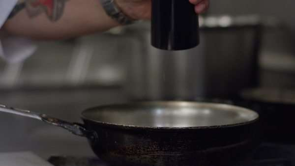 Medium close-up shot of a chef seasoning a food in a pan Royalty-free stock video
