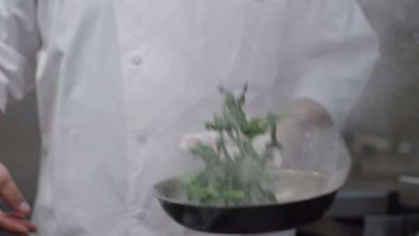Medium close-up shot of a chef placing a steaming pan onto a stove Royalty-free stock video
