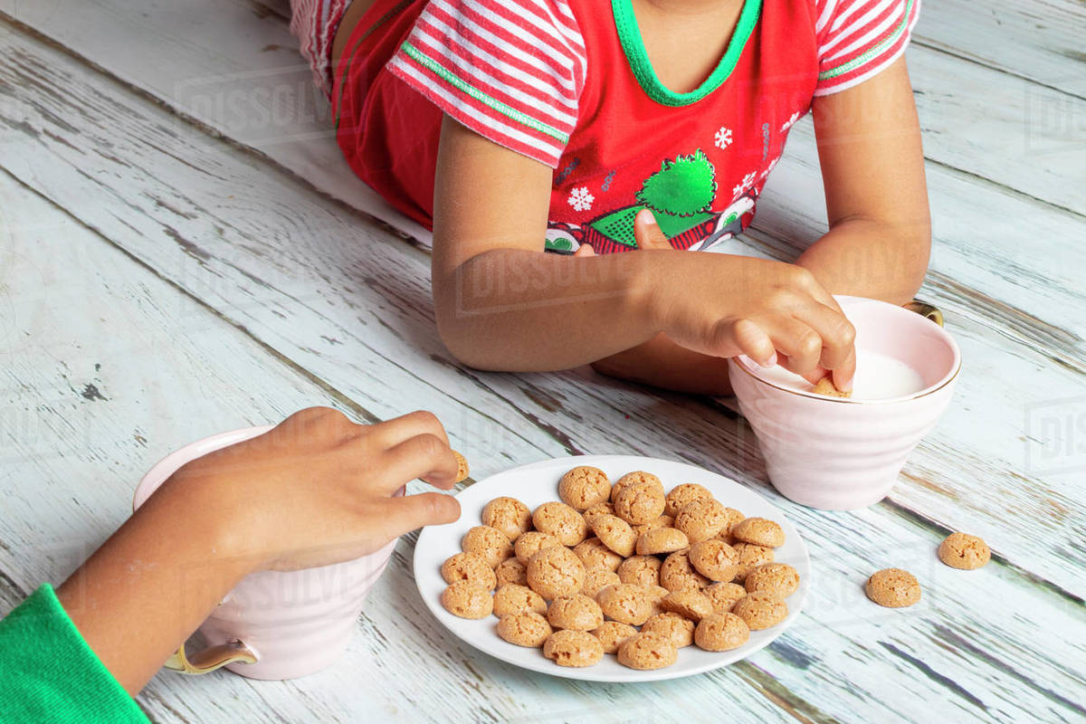 Little sisters eating cookies with milk on Christmas day Royalty-free stock photo