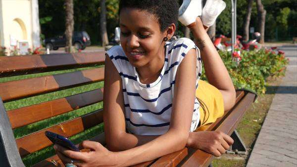 Portrait of a beautiful young woman checking the cell phone in a city park Royalty-free stock video