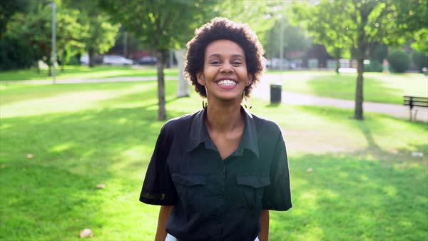 Hand-held shot of a woman laughing into camera in a park Royalty-free stock video