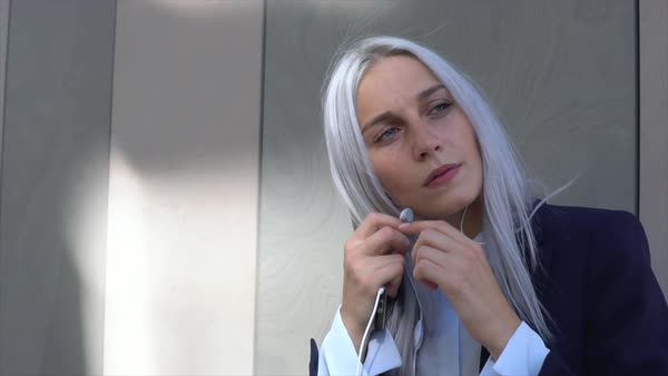 Slow motion shot of a woman inserting earphones into her ears Royalty-free stock video