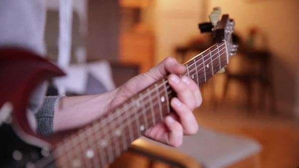 Close-up of a man playing the electric guitar on a couch. Royalty-free stock video
