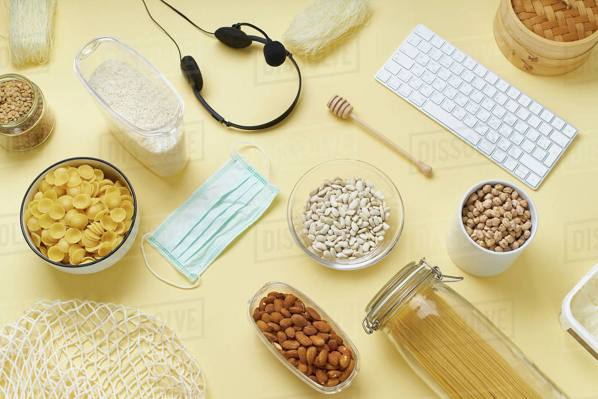 Flatlay with food provision and home office equipment prepared to survive Coronavirus COVID 19 pandemic at the time of cuarentine and home isolation. Pasta, chickpeas, rice, nuts, keyboard and headphone set. Royalty-free stock photo