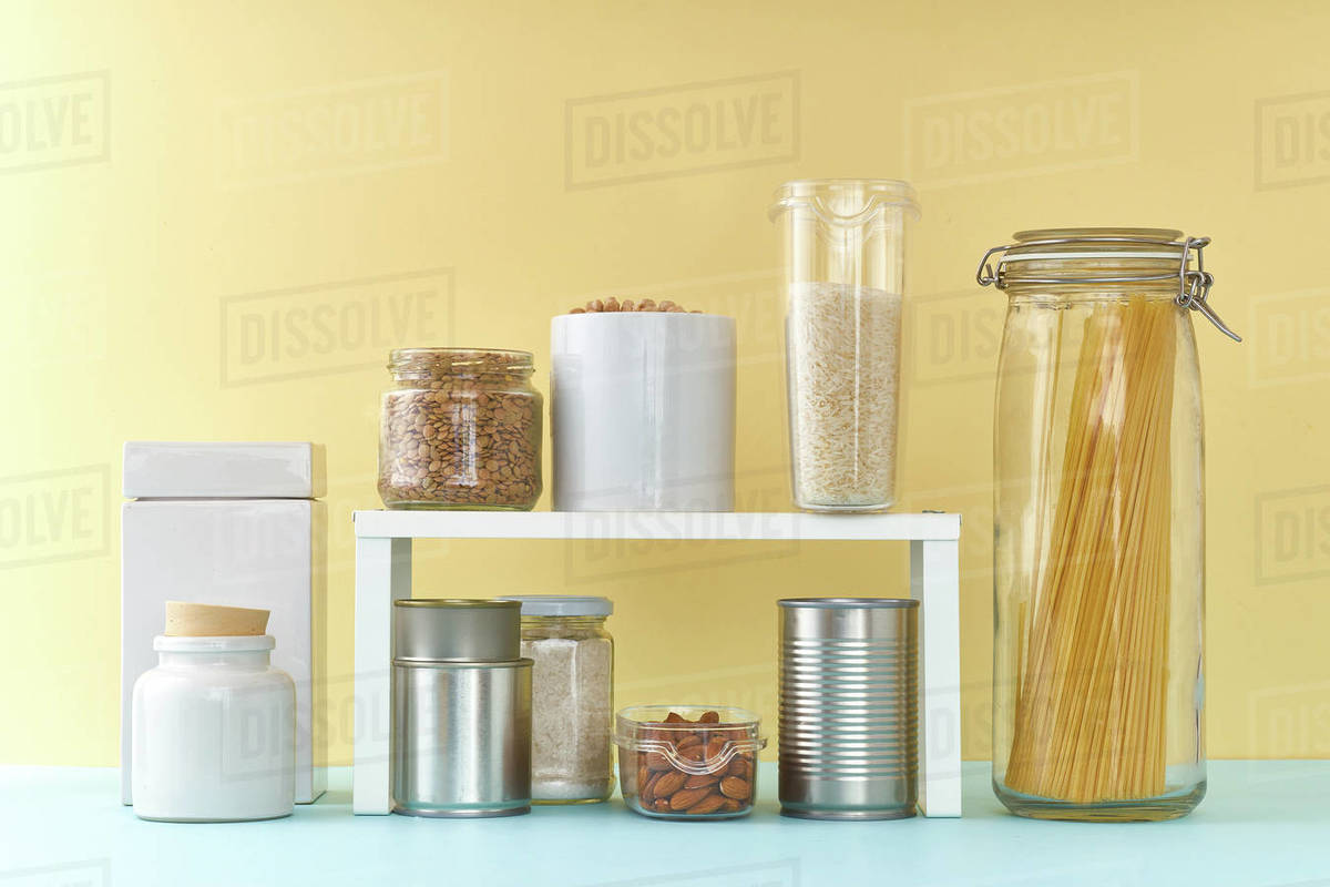 Food staples on pantry shelf prepared to survive Coronavirus COVID 19 pandemic at the time of cuarentine and home isolation. Groceries on colorful background Royalty-free stock photo