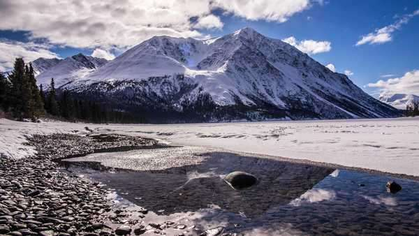 Timelapse of clouds moving over King's Throne Mountain in Kluane National Park, Yukon with reflections in the melting Kathleen Lake Royalty-free stock video