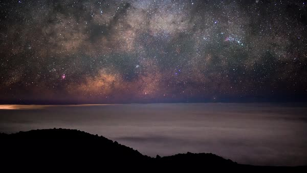 Close up of the Milky Way Core rising over the cloudy horizon below from Mauna Kea volcano Royalty-free stock video