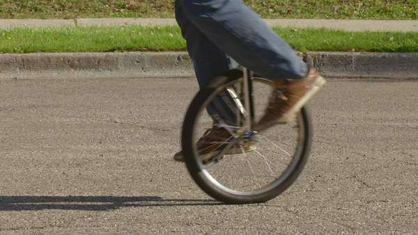 Tilt up from the wheel of a unicycle to the face of the rider as he travels down a suburban street on a sunny spring day in the American Mid West. Medium shot Royalty-free stock video