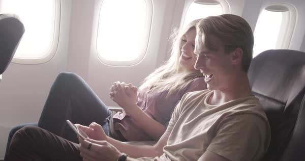 Attractive young couple enjoy watching online content on a smart phone as they fly in main cabin of commercial jet airliner. Medium shot from side angle, recorded hand-held Royalty-free stock video
