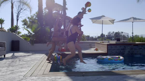Group of friends jump together into a swimming pool, creating a big splash at a resort location with  palm trees and umbrellas behind.  Side view, slow motion Royalty-free stock video