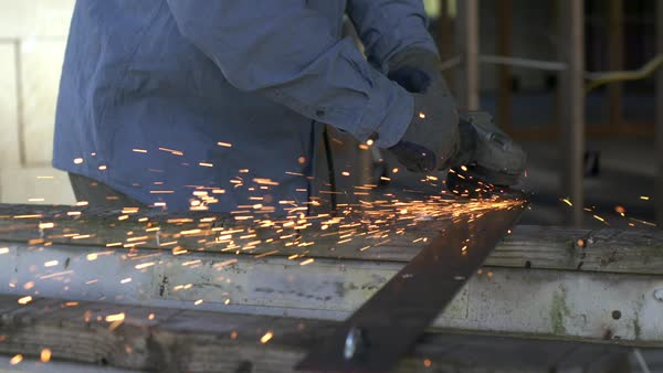 Workman using angle grinder on a piece of metal, creating a shower of sparks inside a house under construction Royalty-free stock video