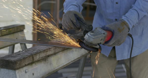 Detail of workman using angle grinder on a piece of metal, creating a shower of sparks inside a house under construction Royalty-free stock video