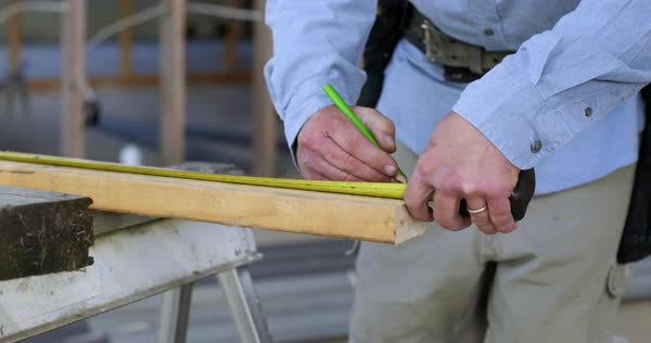 Detail of a contractor measuring and marking up a piece of wood with a pencil, ready to saw inside home under construction Royalty-free stock video