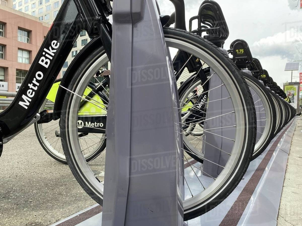 LOS ANGELES, CA, MAR 2020: wheel-high view of black and green LA Metro Bike Share rental bicycles lined up in dock near museums in Downtown. Emphasis on logo Royalty-free stock photo
