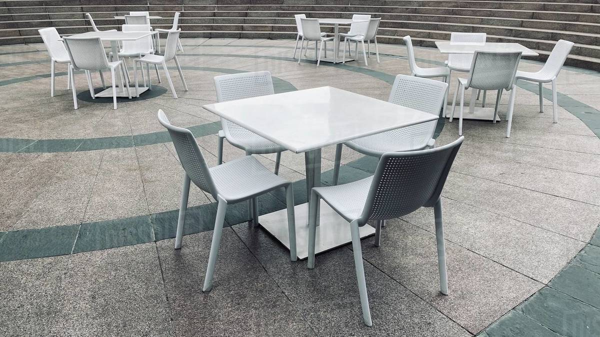 """LOS ANGELES, CA, MAR 2020: empty white-coated steel chairs and tables, normally full of business people, in Downtown during coronavirus, Covid-19 """"stay at home"""" order Royalty-free stock photo"""