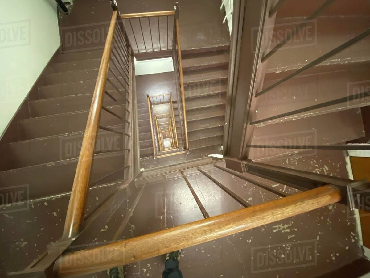 Looking down several floors through interior fire-escape staircase. Brown painted steps with chipped paint, wooden bannister railings and pale green walls Royalty-free stock photo