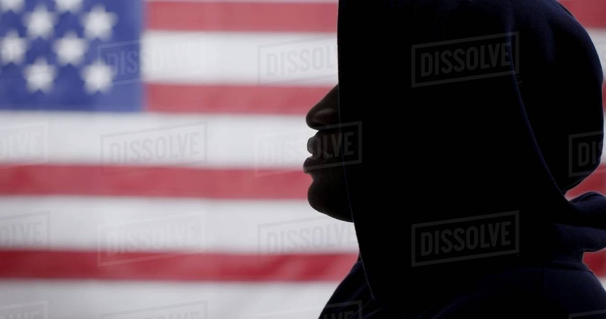CU silhouetted African American man in a  hoodie, face in profile, with US flag in background Royalty-free stock photo