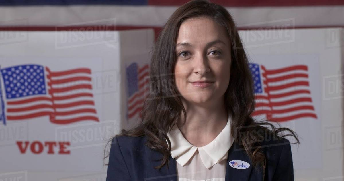 """Close up Caucasian businesswoman in smart jacket wearing """"I Voted"""" sticker in front of polling booths with US flag on wall Royalty-free stock photo"""