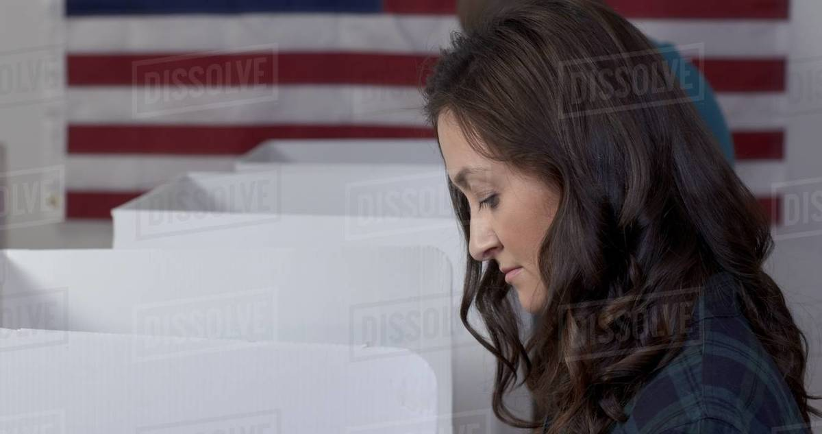 CU side view Caucasian woman voting with African American man behind her in booths at polling station Royalty-free stock photo