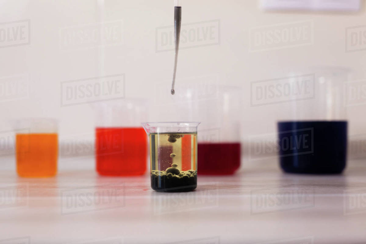 By adding drops of coloured water to a beaker with oil. Science experiment Royalty-free stock photo