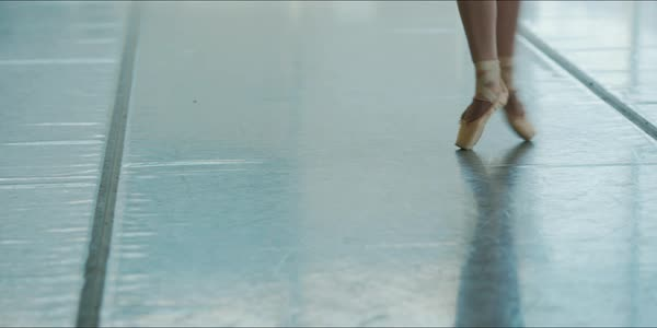 Hand-held shot of a ballerina wearing pointe shoes dancing in a studio Royalty-free stock video